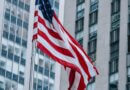 american flag waving against contemporary skyscrapers